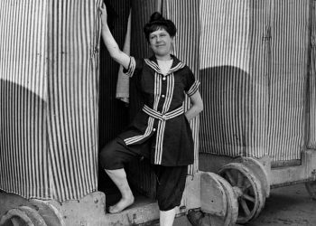 """1910 - Открит е железопътният транспорт, на хората се отдава възможността да пътуват надалеч, което помага на туризма и развитието на курортите. Представителите на висшата класа, обаче, не са свикнали да се събличат публично. Така че трябва да измислят дрехи, с които да прекарват времето си на плажа. Първият женски бански костюм се състои от топ и широки панталони. Мъжете пък са облечени с панталони до коленете и топ, който да прикрива косматите им гърди. Друга интересна подробност от плажа в началото на 20-ти век са """"машините за къпане"""". Това е мястото, където хората се преобличат и след това се втурват в океана. Машините се местят по релсите с помощта на коне. EAST NEWS"""